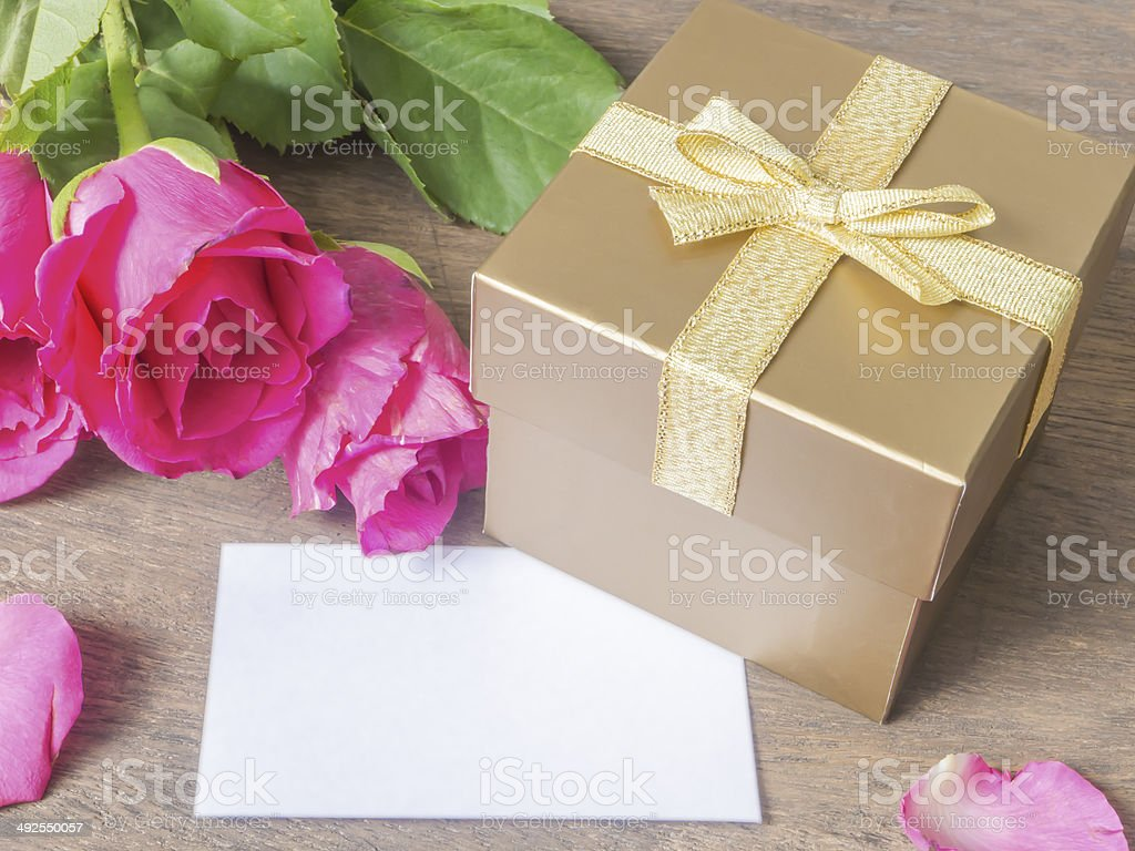 Gold gift box with card and rose on wooden table