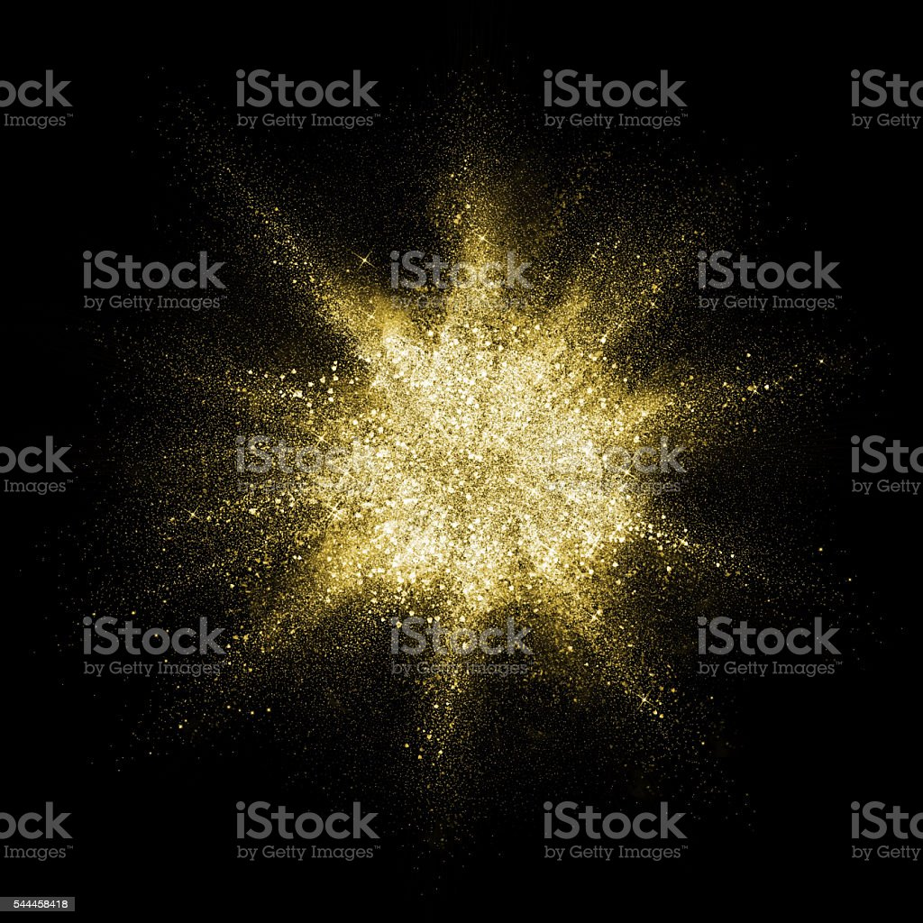 Gold glitter powder explosion. Golden color dust splash. stock photo
