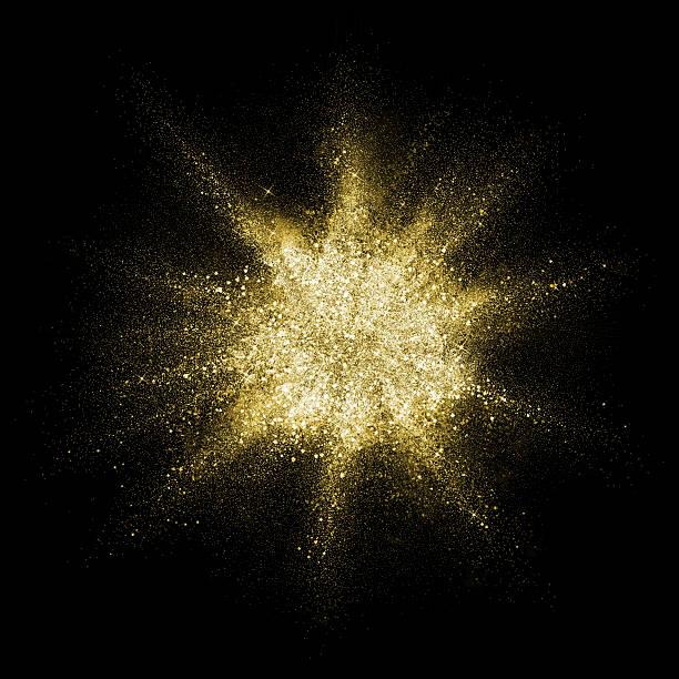Gold glitter powder explosion. Golden color dust splash. stock photo