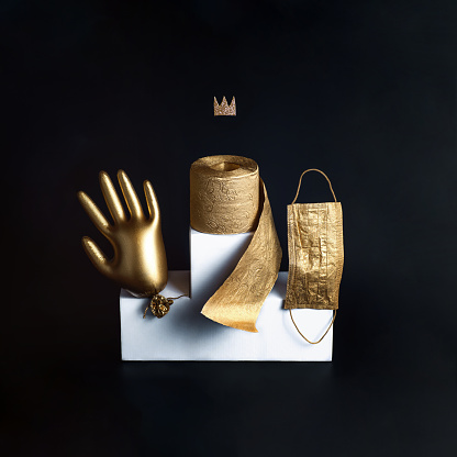 Gold glove, toilet paper and a mask on a white bollard. Concept on the theme of coronavirus trends. Black background.