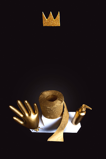 Gold glove, toilet paper and a sanitizer on a white bollard. Concept on the theme of coronavirus trends. Black background.