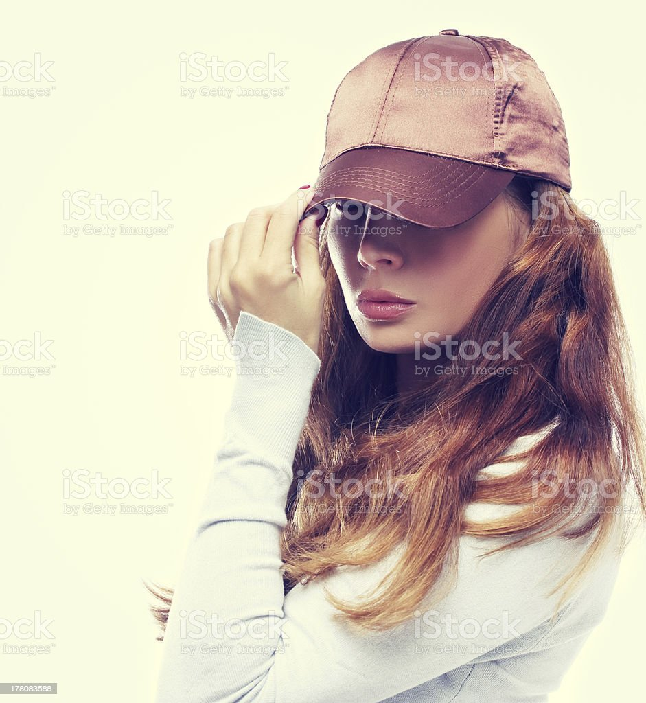 Gold haired girl with cap on blue background royalty-free stock photo