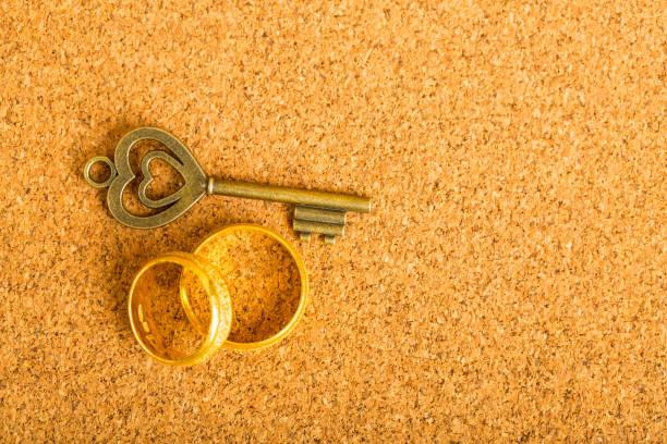 gold herz schlüssel und verlobungsring - schlüssel dekorationen stock-fotos und bilder
