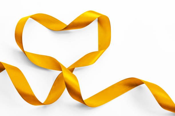 goldenes herz band isoliert auf weißem hintergrund (clipping-pfad) symbolischen bogen farbkonzept sensibilisierung der öffentlichkeit für die kinderkrebsforschung - weihnachtsspende stock-fotos und bilder
