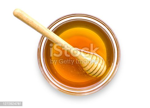 istock Gold honey with wooden honeycomb in glass bowl isolated on white 1272524781