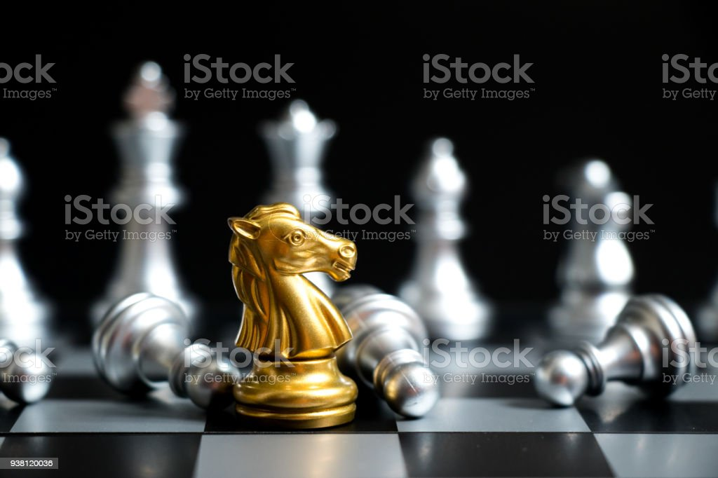 Gold horse in chess game face with the another silver team on black background (Concept for company strategy, business victory or decision) stock photo