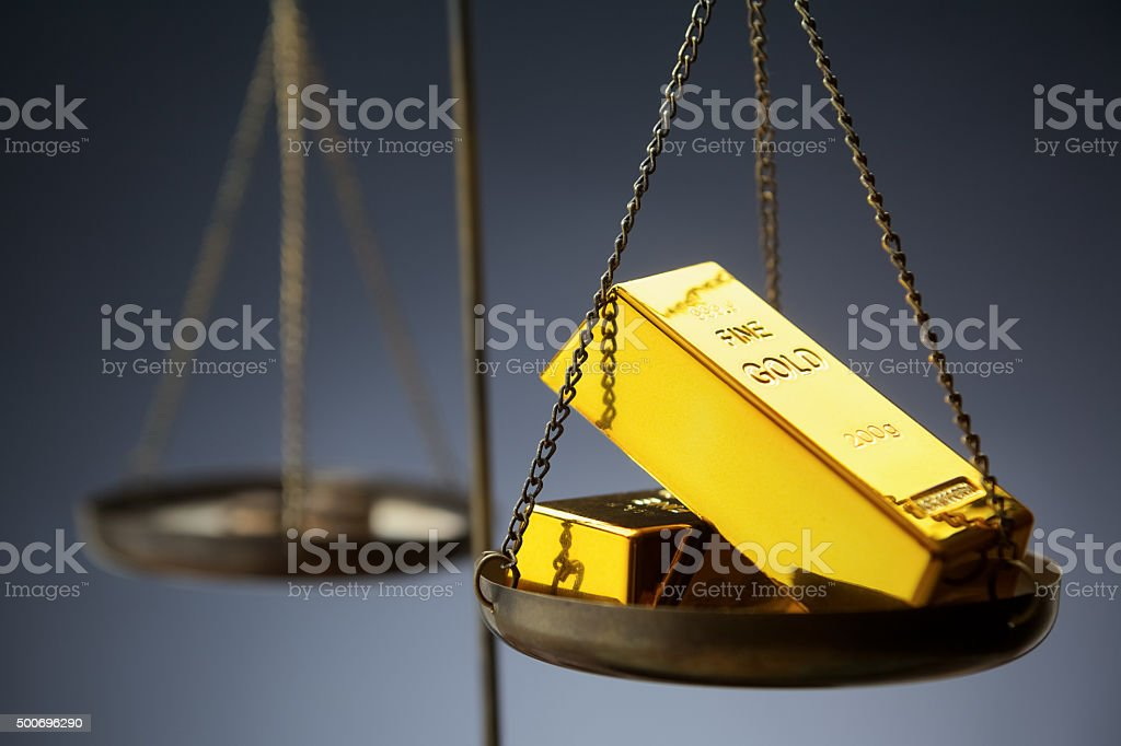 Gold ingots on brass scale stock photo