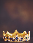 istock Gold jeweled crown on velvet 1227603889