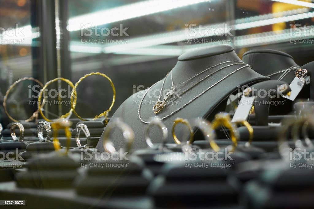 Gold jewelry diamond shop with rings and heart shape necklaces in luxury retail store stock photo