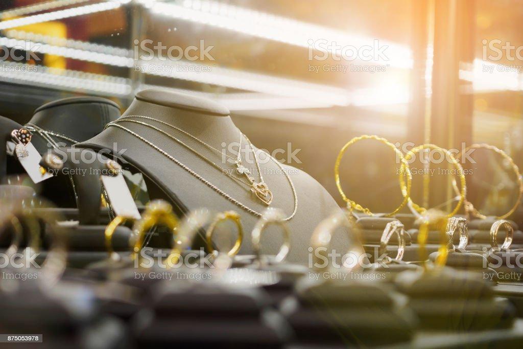 Loja de joias de ouro diamante com anéis e colares de forma de coração em loja de varejo de luxo - foto de acervo