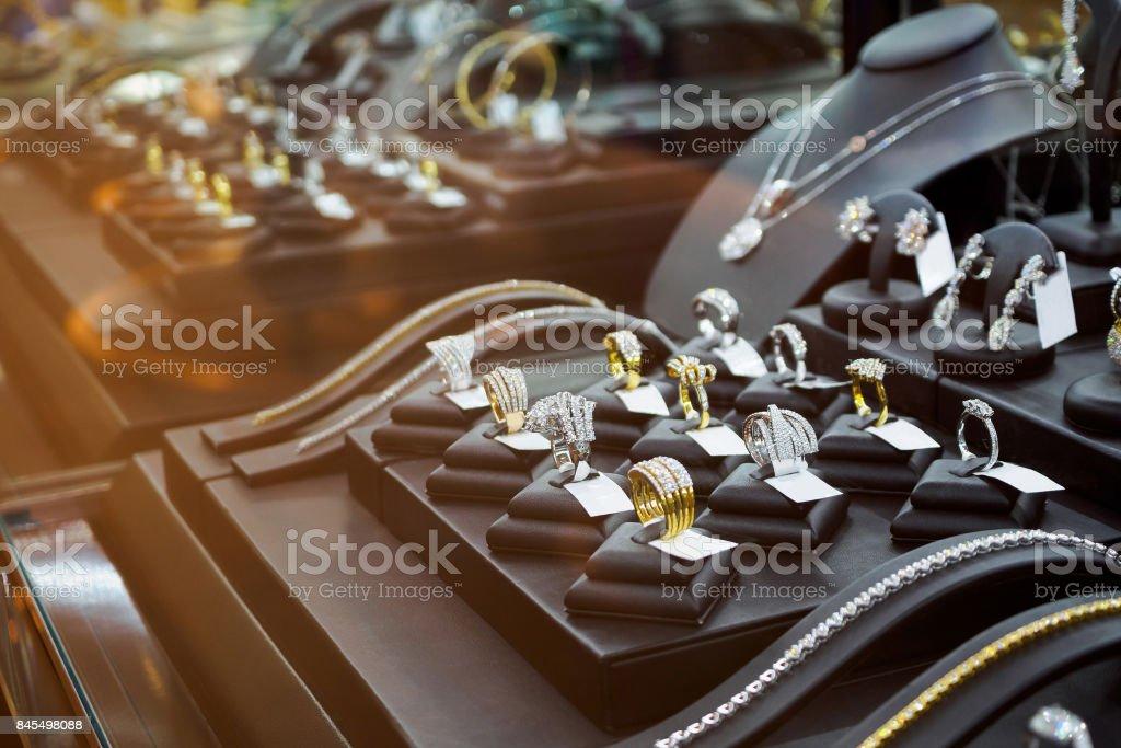 Gold jewelry diamond shop with rings and necklaces luxury retail store window display showcase - Zbiór zdjęć royalty-free (Biżuteria)