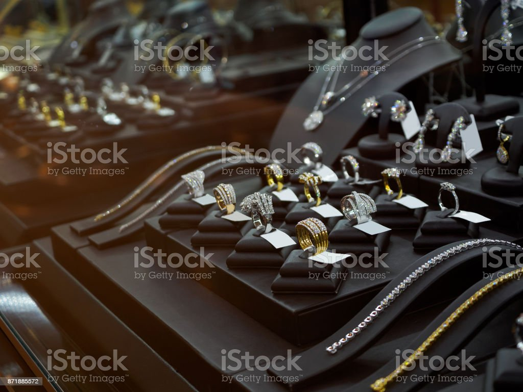 Gold jewelry diamond shop with rings and necklaces luxury retail store window display stock photo