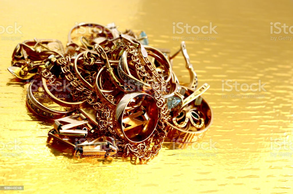 gold jewelry, folded pile on a gold background and brightly lit stock photo
