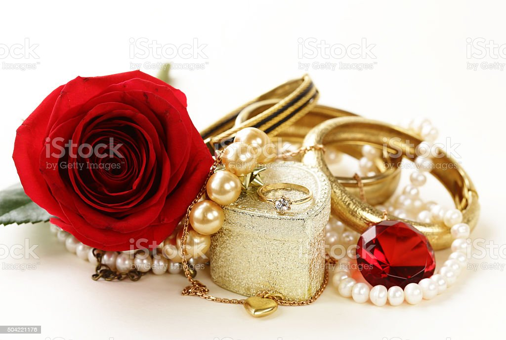 gold jewelry (pearls, necklace, ring) with roses on a white stock photo