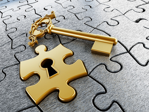 Gold jigsaw puzzle piece and key standing on gray puzzle piece background.