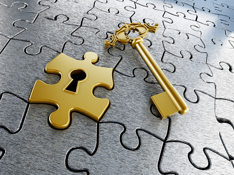 Gold jigsaw puzzle piece and key on puzzle background.