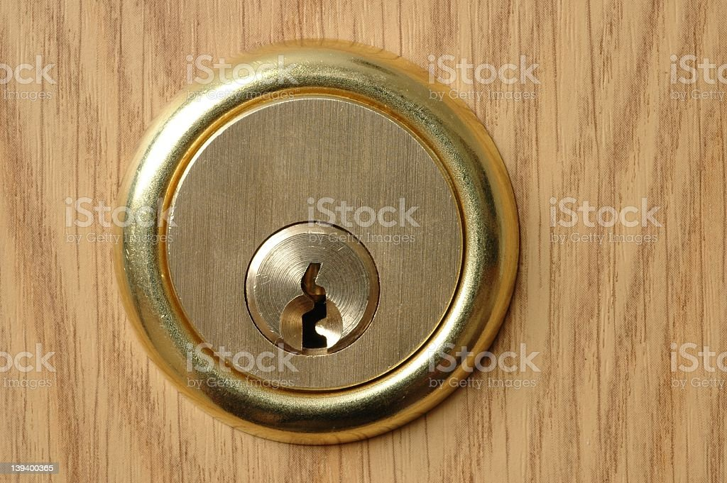 Gold key lock on a wooden door stock photo