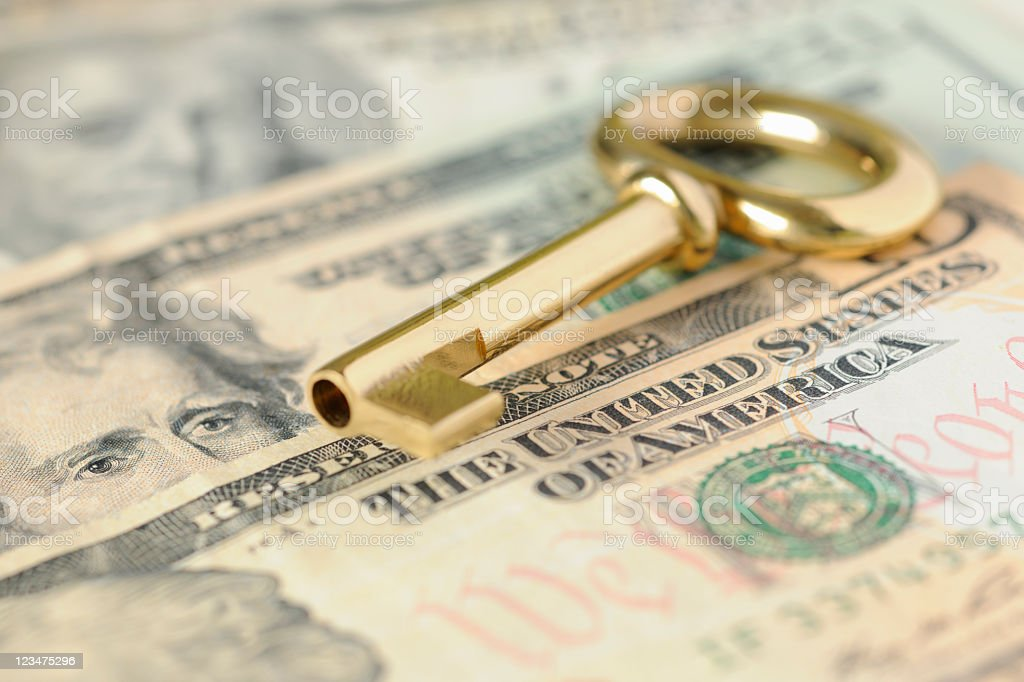 Gold Key to Success over United States Dollars in Cash stock photo