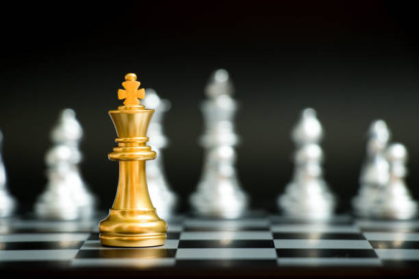 gold-könig im schach spiel gesicht mit einem anderen silber-team auf schwarzem hintergrund (konzept für unternehmensstrategie, business sieg oder entscheidung) - könig stock-fotos und bilder