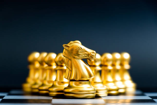Gold knight chess piece stand in front of pawn on black background Gold knight chess piece stand in front of pawn on black background trabajo en equipo stock pictures, royalty-free photos & images