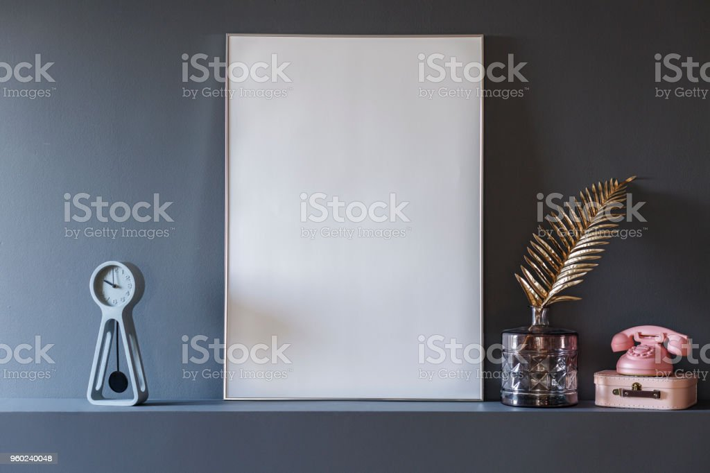 Gold leaf and pink phone next to empty white poster with mockup in grey interior stock photo