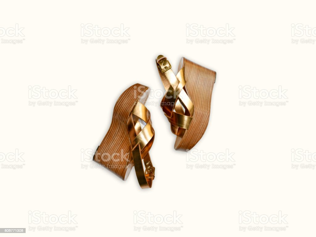 Gold leather trendy woman sandals isolated on bright background. stock photo