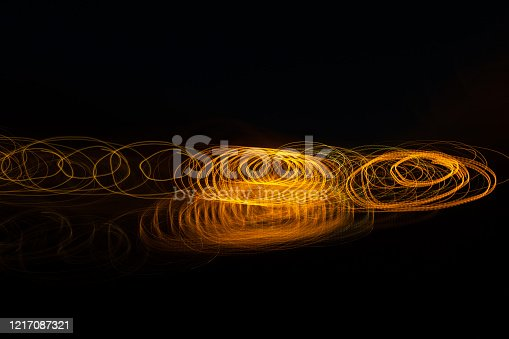 Gold light painting photography, long exposure photo of golden fairy lights in a loop against a black background. Light painting - blurred lights background light paths