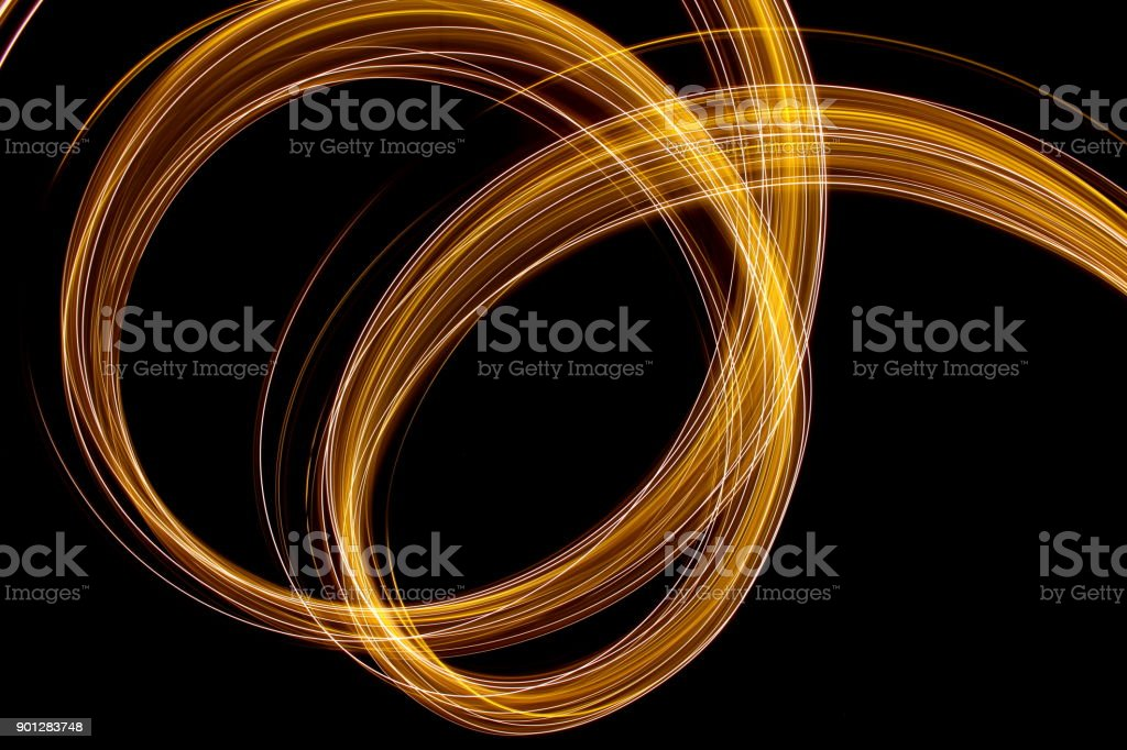 A long exposure photograph of metallic gold fairy lights in a swirly,...