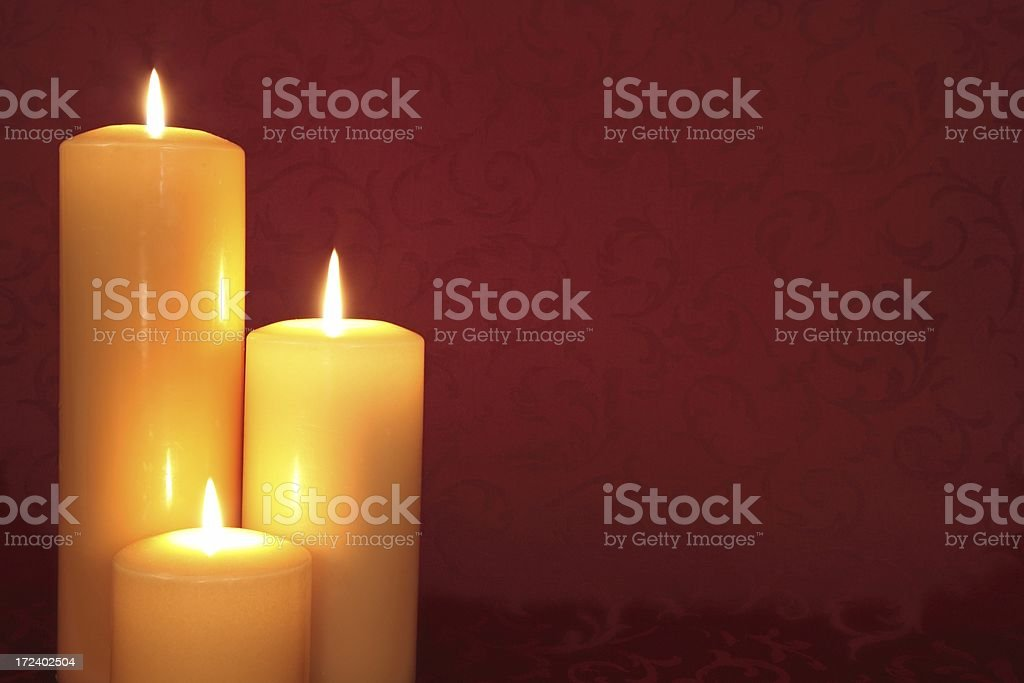 Gold lit Candle Trio on Red background royalty-free stock photo