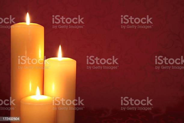 Gold Lit Candle Trio On Red Background Stock Photo - Download Image Now