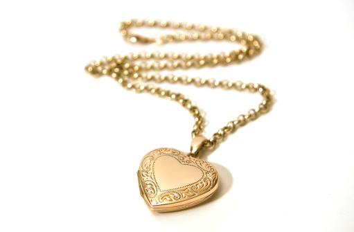A gold locket on a chain. Shallow depth of field - focus on the locket.