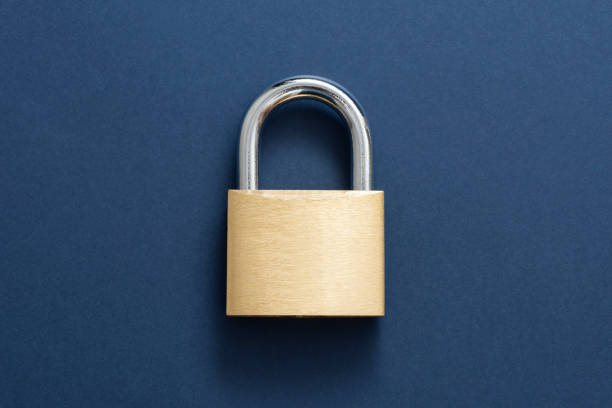 Gold Lockpad Padlock Locked golden padlock on the blue background. padlock stock pictures, royalty-free photos & images