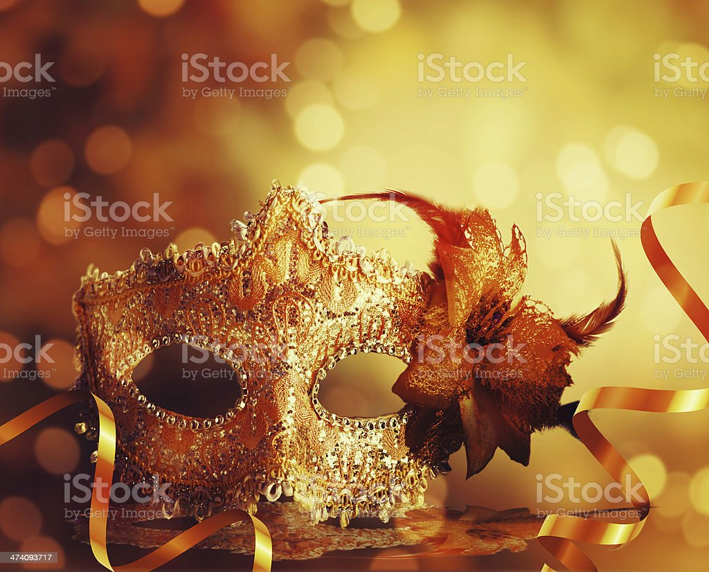 A gold masquerade mask against a golden background royalty-free stock photo