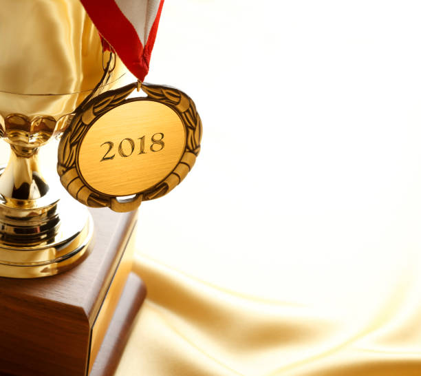 gold medal and trophy engraved with 2018 - award stock photos and pictures