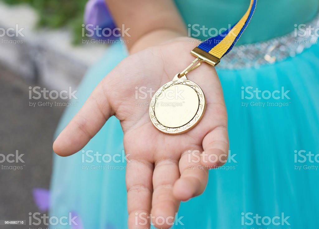 Gold medal at girl hand. Graduated from kinder garden royalty-free stock photo