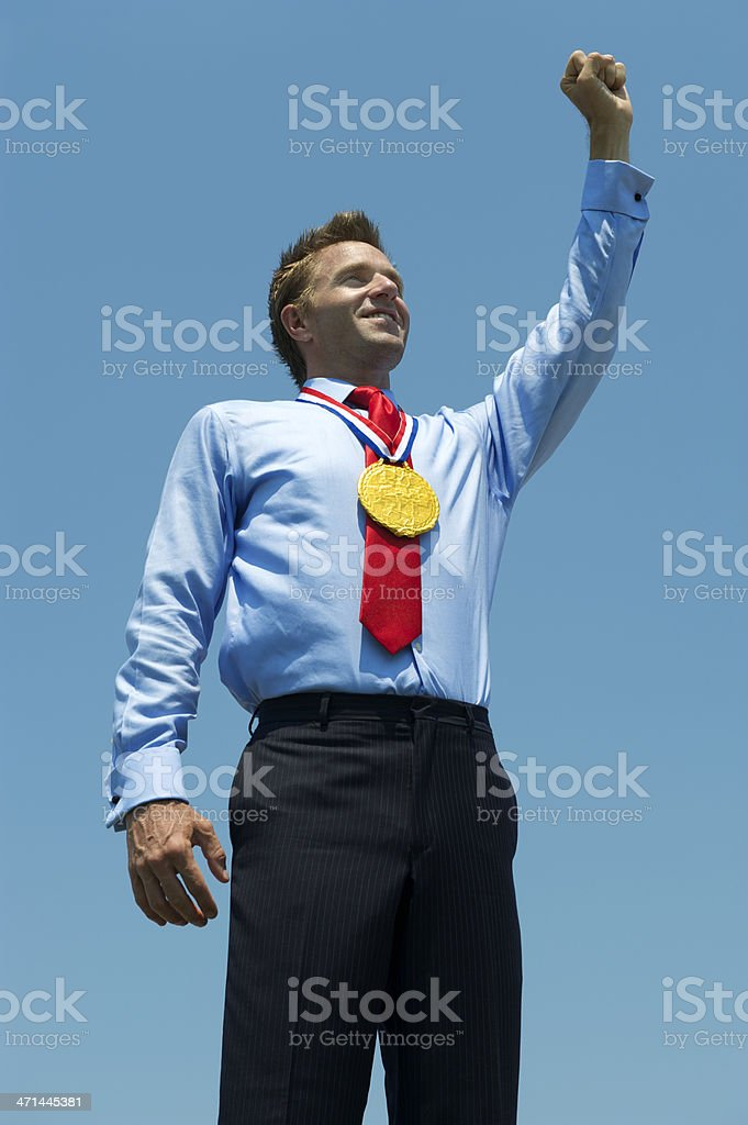 Gold Medal Businessman Pumps His Fist in Blue Sky royalty-free stock photo