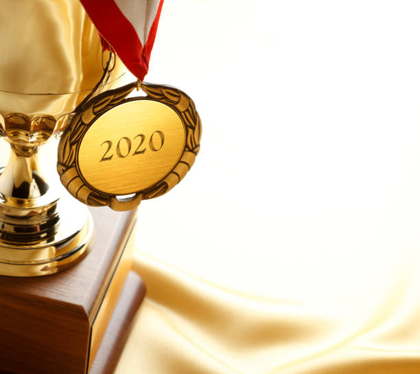 Gold Medal Engraved With 2020 Hangs From A Gold Trophy A gold medal hanging on a trophy with 2020 engraved on the medal.  Trophy is sitting on soft golden satin that provides ample room for copy and text. win stock pictures, royalty-free photos & images