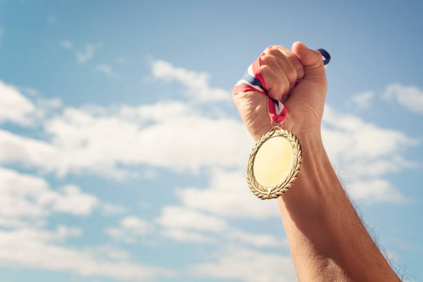 Gold medal held in hand raised against sky background stock photo
