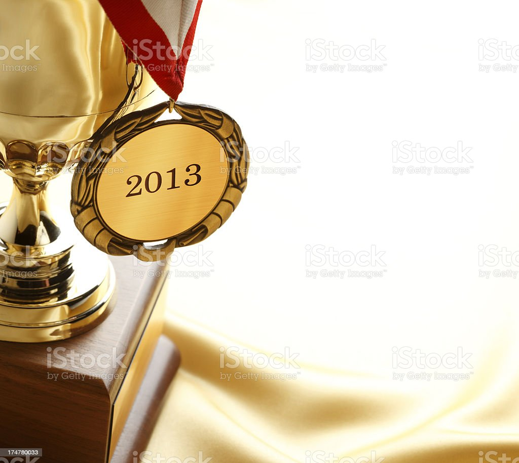 Gold medal inscribed with 2013 hanging from a trophy royalty-free stock photo