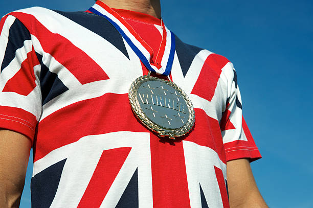 """Gold Medal Union Jack British Flag T-Shirt """"London, UK - June 14, 2012: Big shiny winner medal hangs on bright Union Jack British flag t-shirt. This is a staged concept shot to illustrate national pride of the host country for the Summer Olympic Games. 2012 is the third time the UK hosts the event."""" 2012 stock pictures, royalty-free photos & images"""