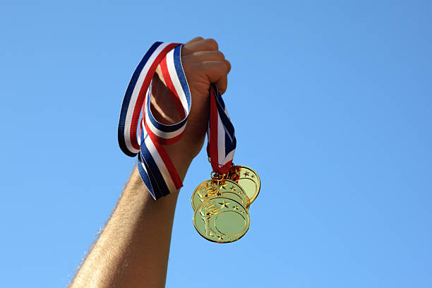 Gold medal winner Winning at olympic games, hand holding gold medals medal stock pictures, royalty-free photos & images