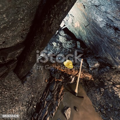 A miner's safety helmet and pick axe lie on a collapsed support timber at the end of an abandoned gold mine.
