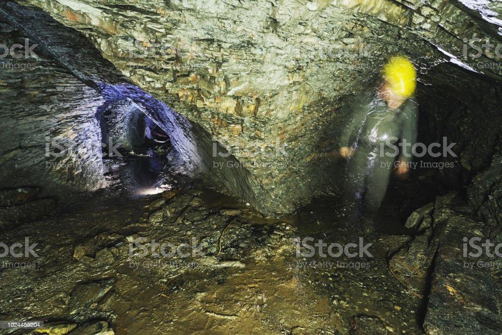 Miner inside an abandoned gold mine adit.