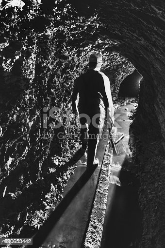 A gold miner is silhouetted in the narrow shaft of an abandoned gold mine.