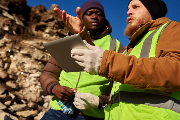 Gold Miners Inspecting Land Low angle portrait of two industrial workers wearing reflective jackets, one of them African, inspecting mineral mines on worksite outdoors and using digital tablet frontier field stock pictures, royalty-free photos & images