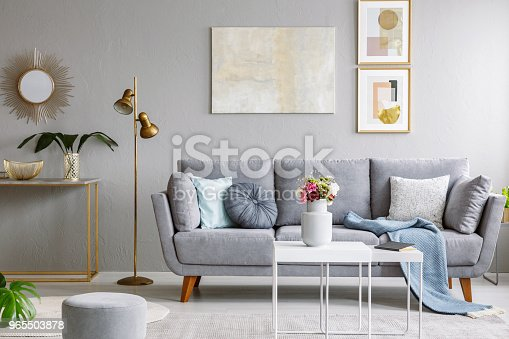 Gold mirror above shelf with plant in grey living room interior grey sofa and flowers on table