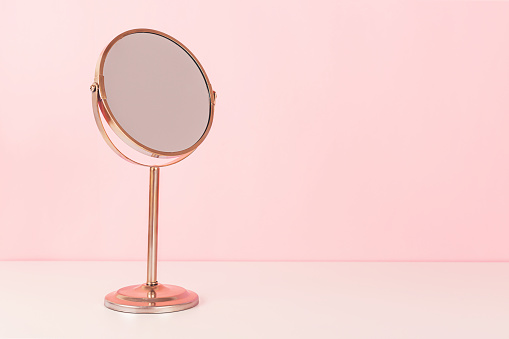 Gold mirroron pink background. Vanity table concept. Minimal composition. Copy space for your text.