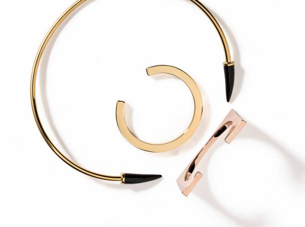 goldene halskette und armbänder isoliert auf weißem hintergrund - a zone armband stock-fotos und bilder