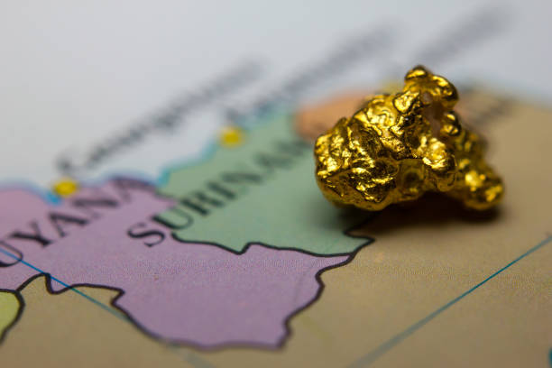 Gold nugget on top of map of Suriname stock photo