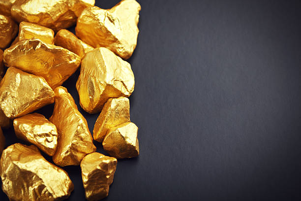 Gold nuggets on a black background. Closeup stock photo